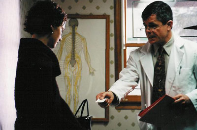 Katie's doctor (Richard Ferrone) hands her a referral card.